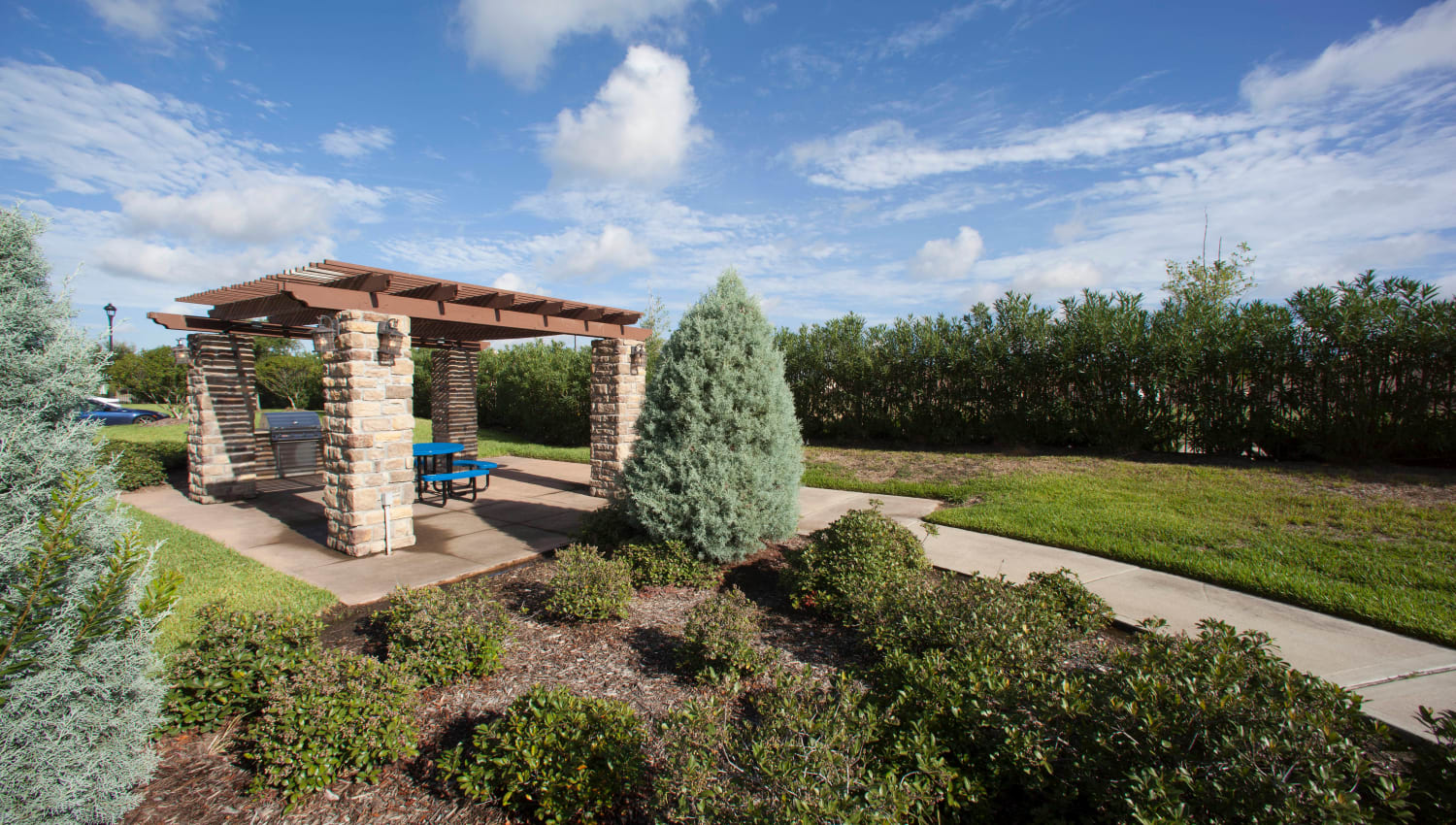 Picnic area surrounded by well-manicured shrubs at Olympus Katy Ranch in Katy, Texas