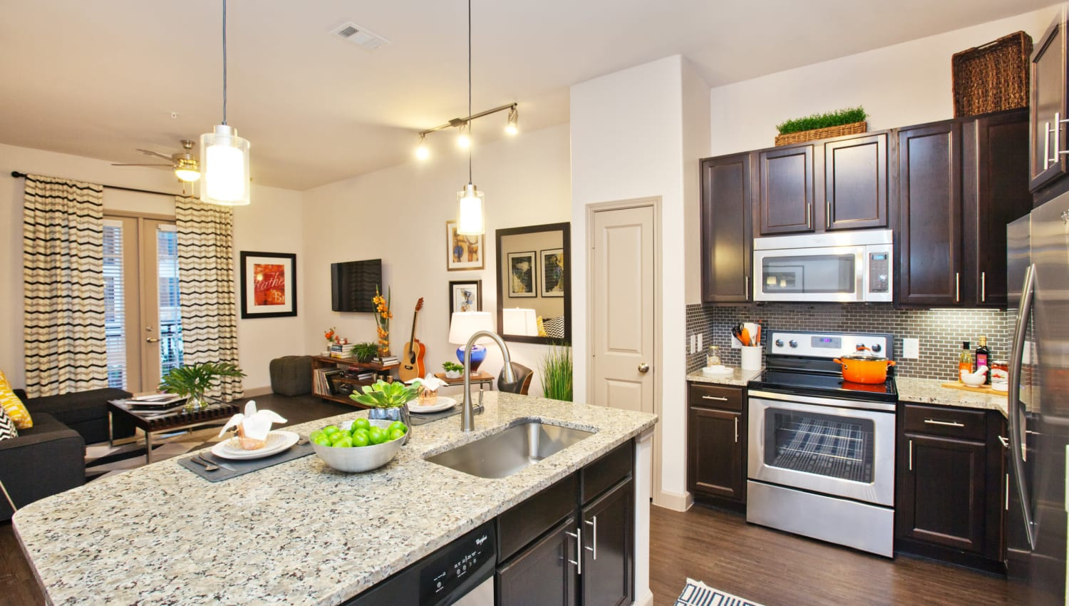 Kitchen island and stainless-steel appliances at Olympus Auburn Lakes in Spring, Texas
