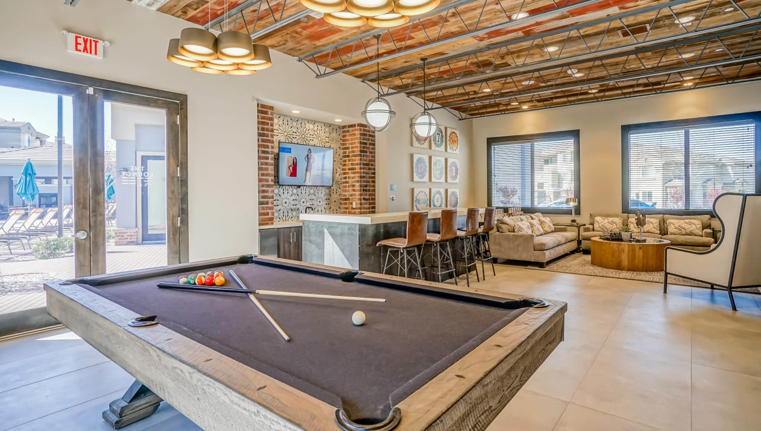 Luxurious game area with a billiards table and lounge seating in the resident clubhouse at Olympus Northpoint in Albuquerque, New Mexico