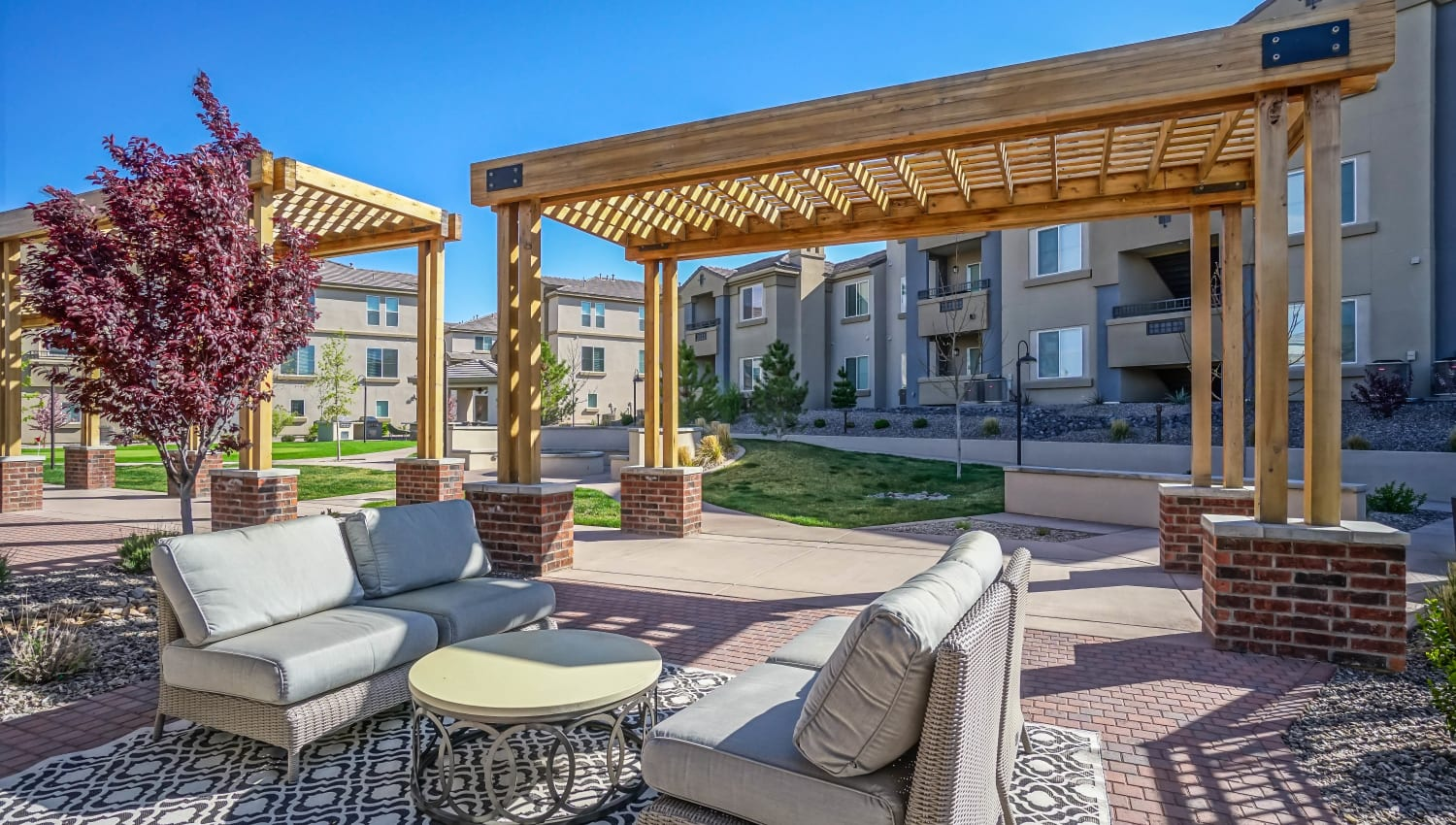 Outdoor lounge with a nearby pergola providing afternoon shade at Olympus Northpoint in Albuquerque, New Mexico
