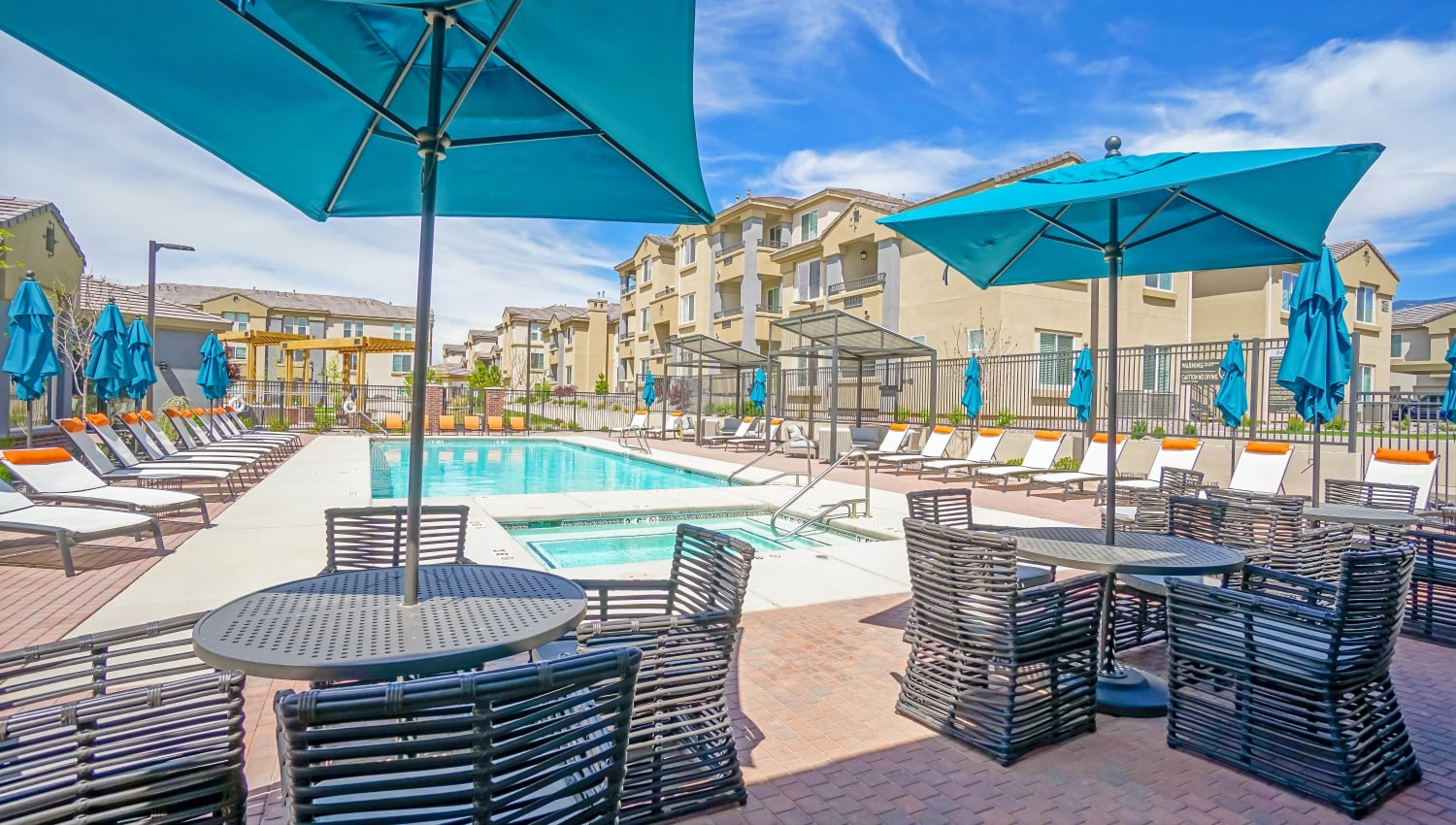 Chaise lounge chairs and shaded seating near the resort-style swimming pool at Olympus Northpoint in Albuquerque, New Mexico