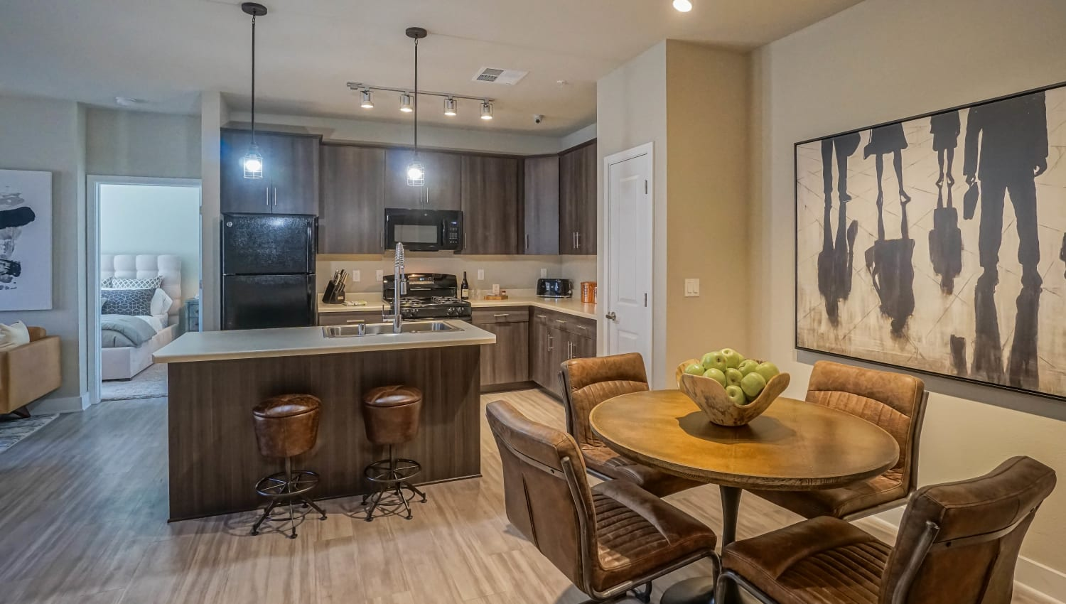 View of the modern kitchen from the dining area of a model townhome at Olympus Northpoint in Albuquerque, New Mexico