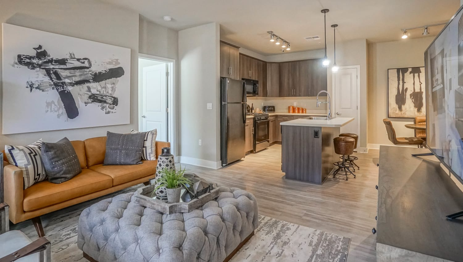 Well-furnished living area with beautiful hardwood flooring in the open-concept layout of a model townhome at Olympus Northpoint in Albuquerque, New Mexico