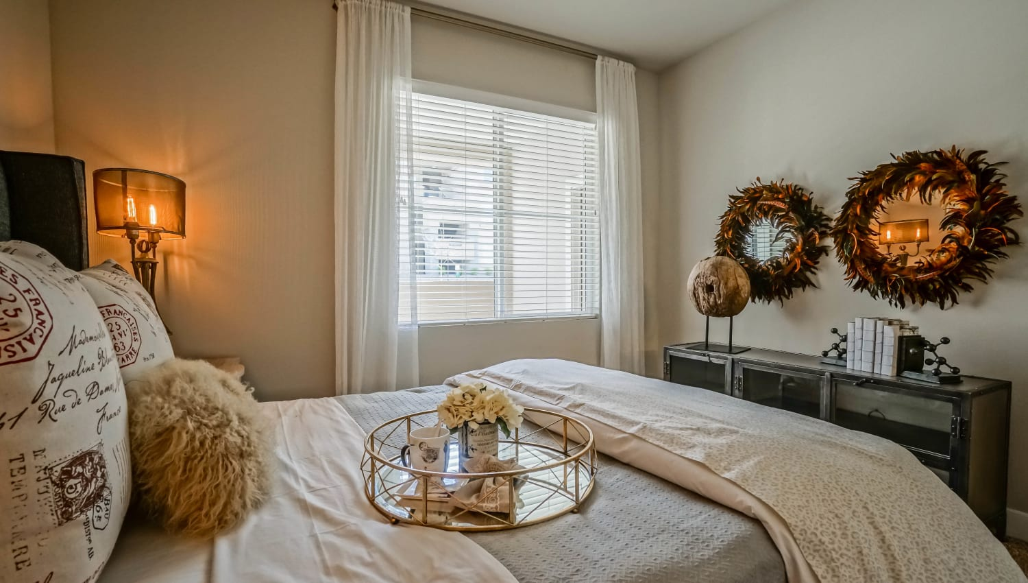 Well-furnished master bedroom with draped windows in a model townhome at Olympus Northpoint in Albuquerque, New Mexico
