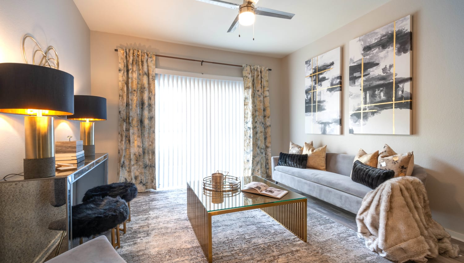 Well-furnished model home's living space with a ceiling fan at Olympus Solaire in Albuquerque, New Mexico