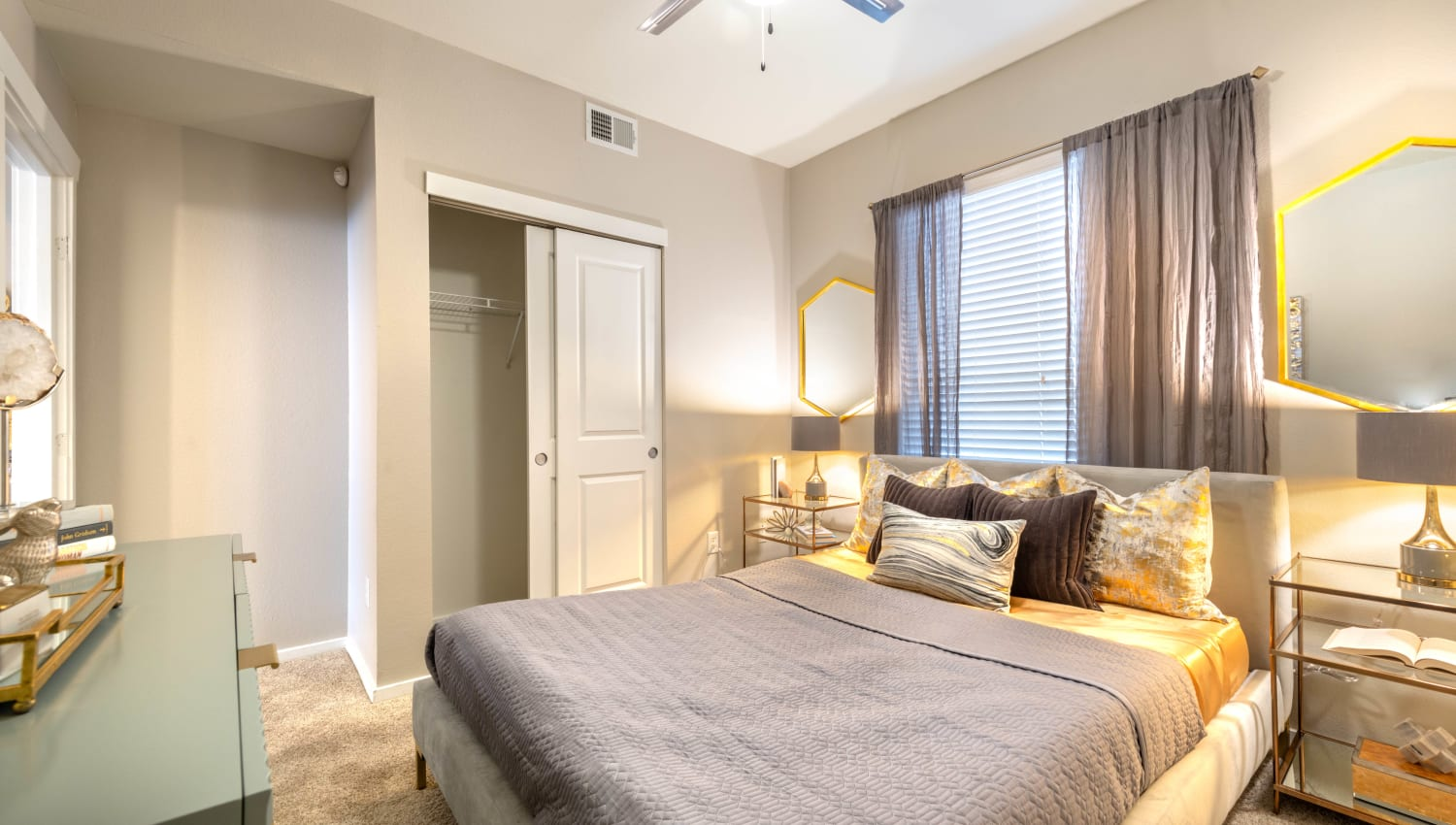 Model apartment's master bedroom with ample closet space and a large bay window at Olympus Solaire in Albuquerque, New Mexico