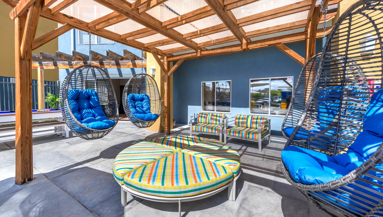 Outdoor lounge area with hanging basket chairs at Olympus Solaire in Albuquerque, New Mexico