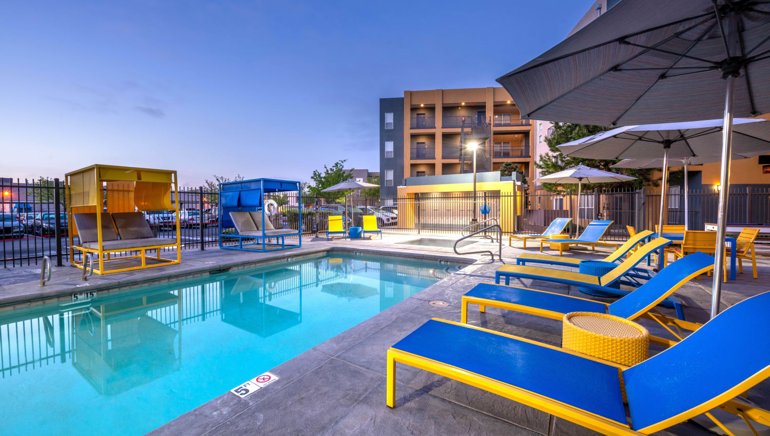 Serene swimming pool flanked by lounge chairs at dusk at Olympus Solaire in Albuquerque, New Mexico