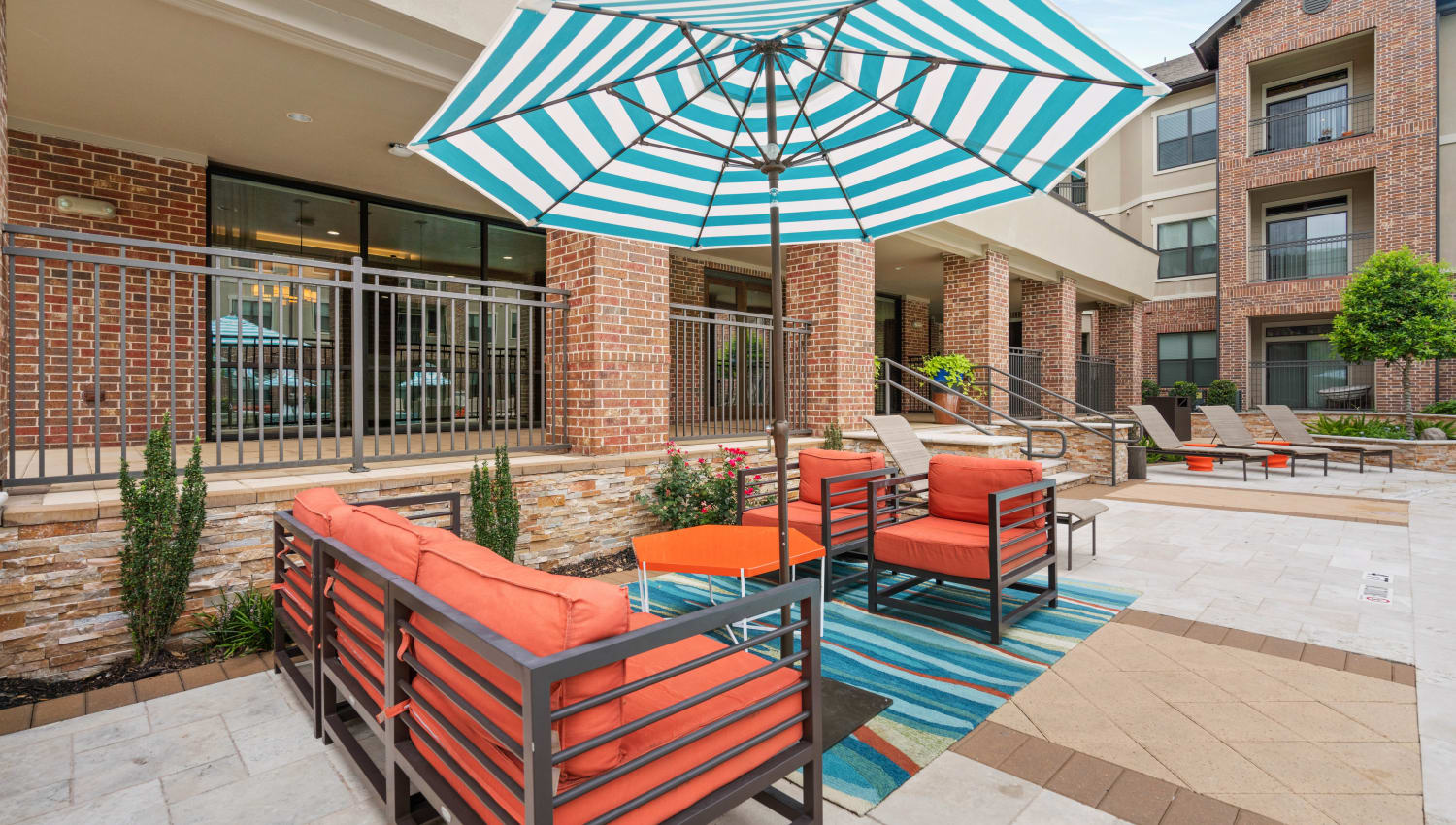 Umbrella providing shade at one of the outdoor lounge areas at Olympus Sierra Pines in The Woodlands, Texas