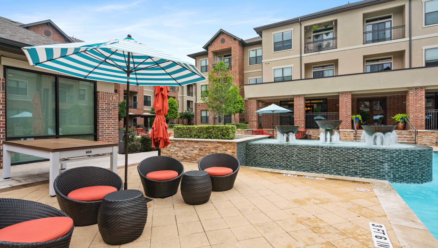 Outdoor lounge near the pool with a fountain at Olympus Sierra Pines in The Woodlands, Texas