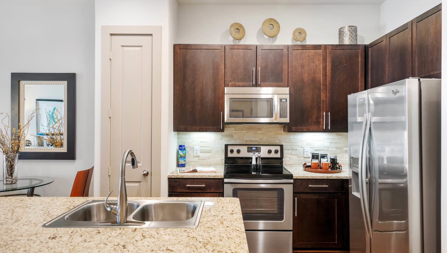 Model apartment's kitchen with a dual-basin sink and stainless-steel appliances at Olympus Sierra Pines in The Woodlands, Texas