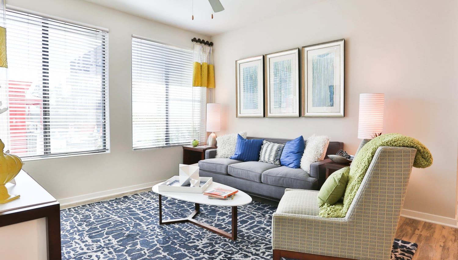Bay windows and classic furnishings in a model home's living area at Olympus Steelyard in Chandler, Arizona