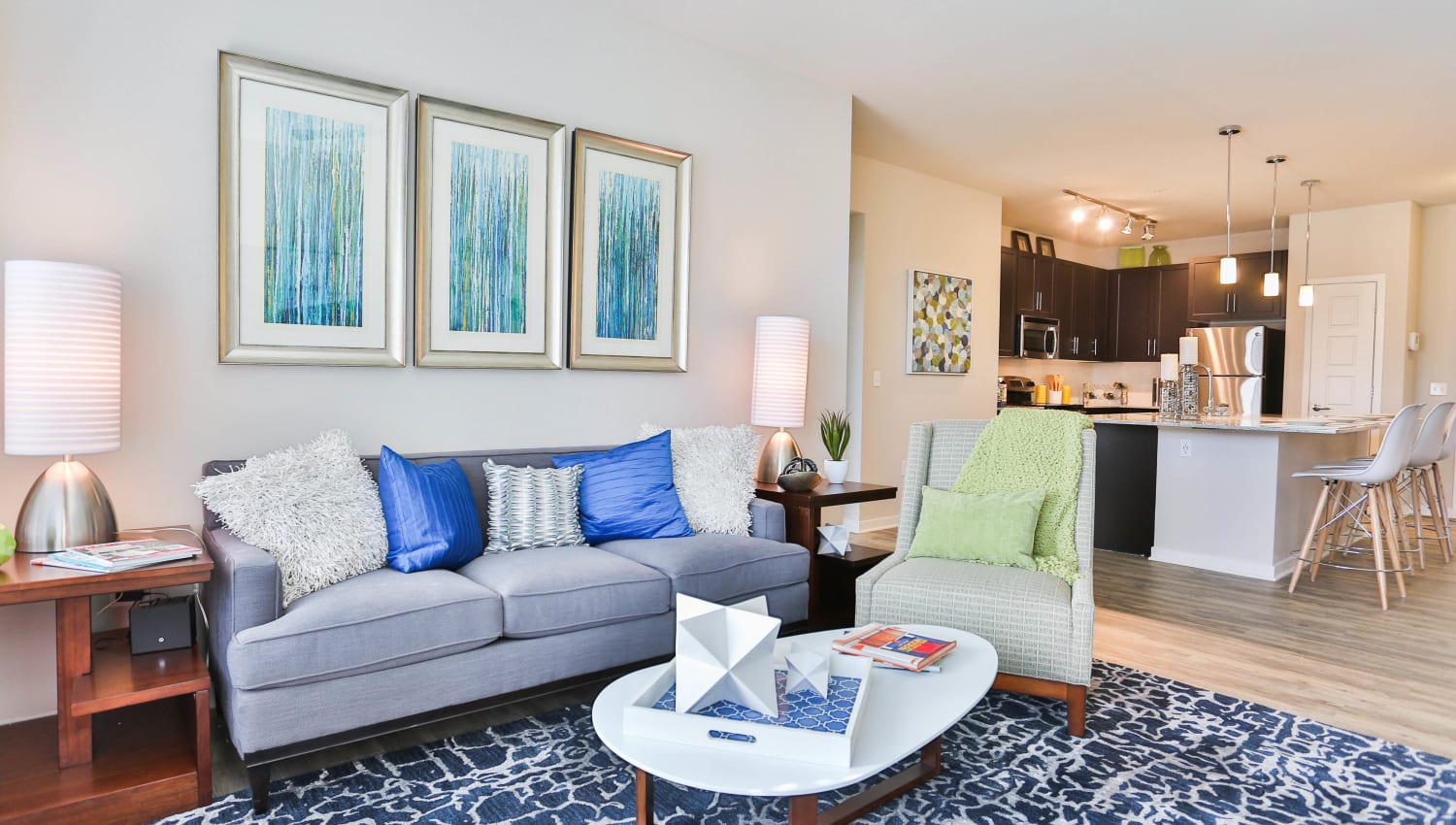 Model apartment with a comfortably furnished living space and a view of the kitchen at Olympus Steelyard in Chandler, Arizona