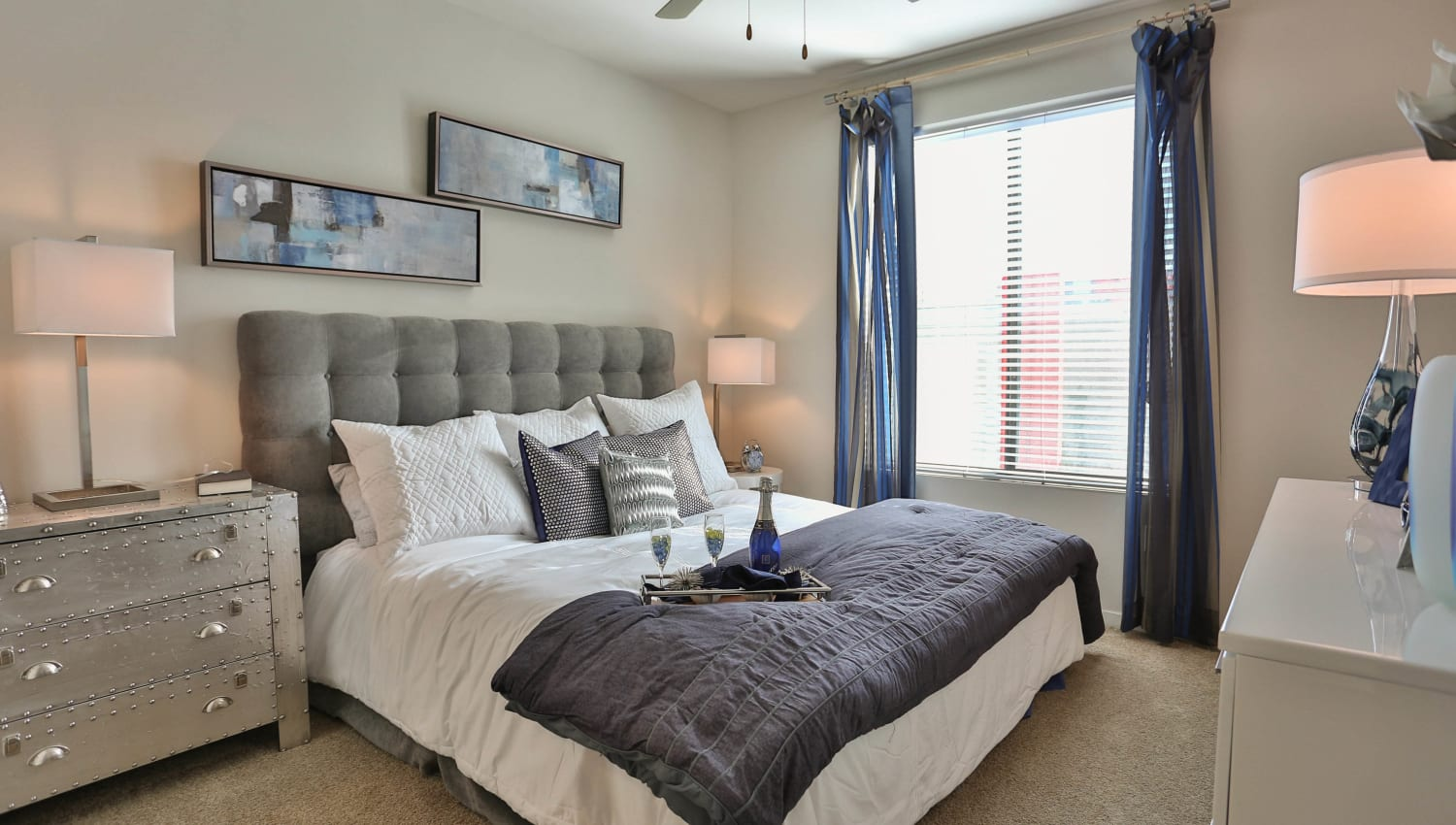 Draped windows and plush carpeting in a model home's master bedroom at Olympus Steelyard in Chandler, Arizona