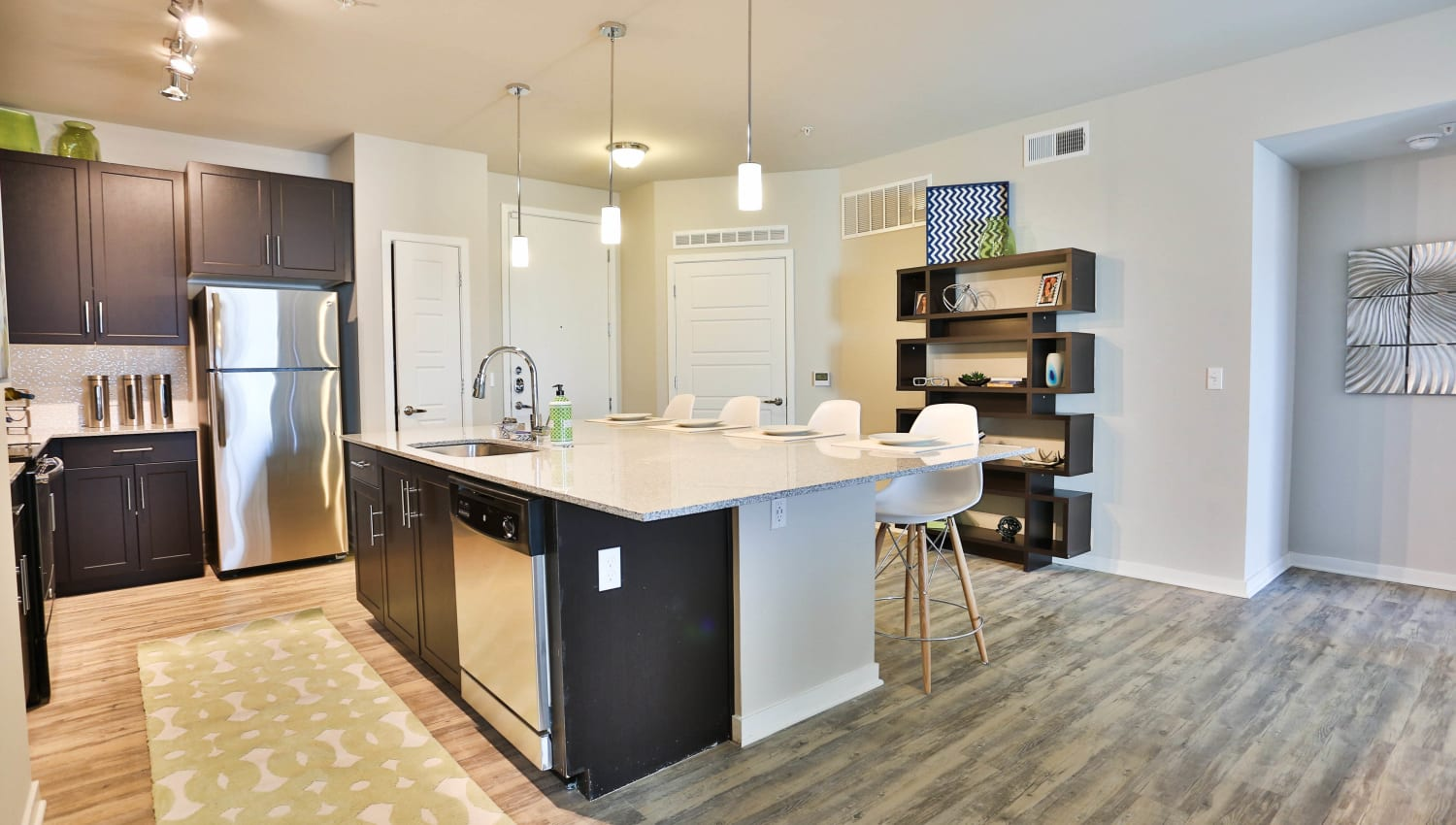 Open-concept gourmet kitchen with rich, dark wood cabinetry in a model apartment at Olympus Steelyard in Chandler, Arizona