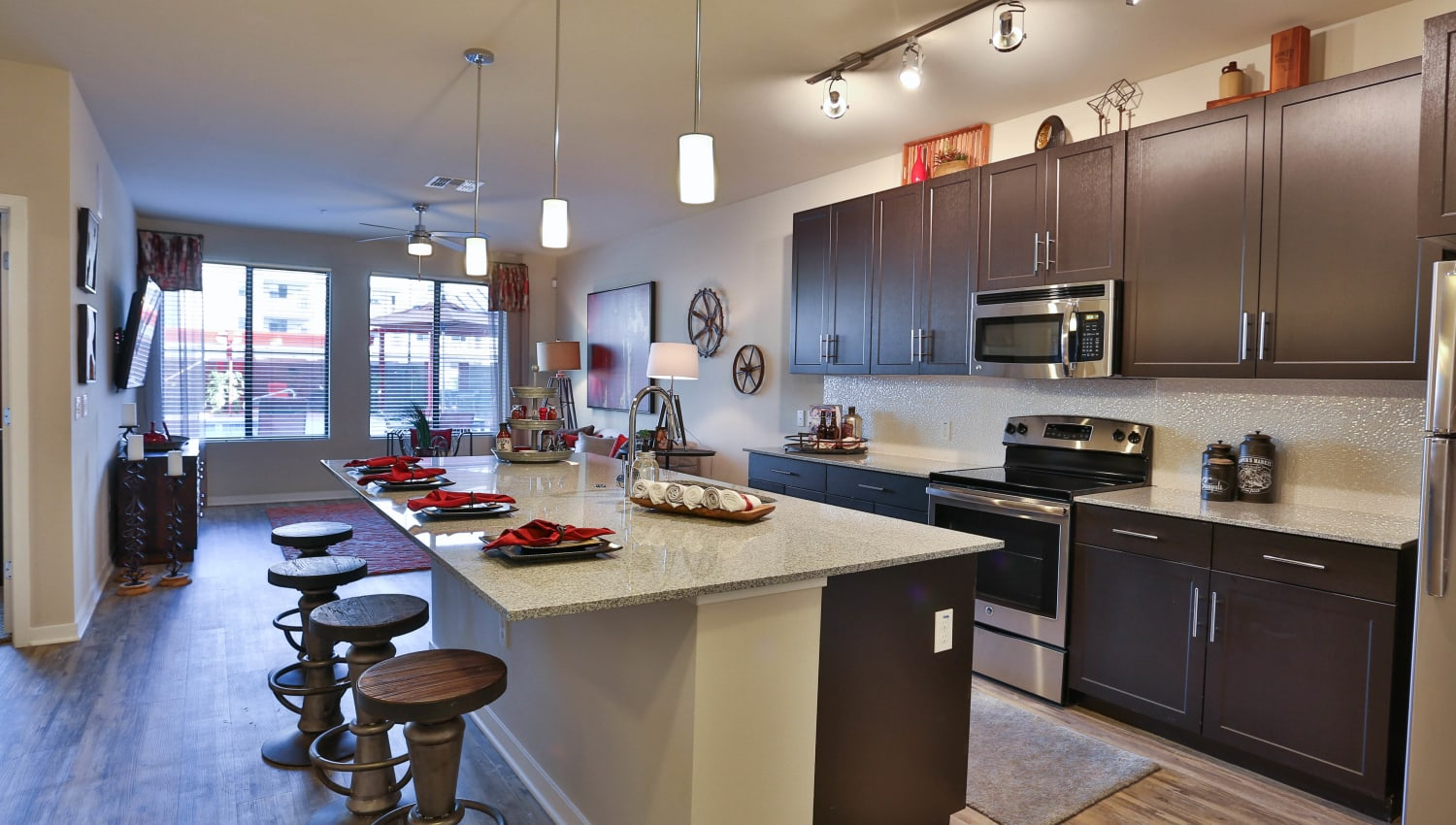 View of the living area from a model apartment home's kitchen at Olympus Steelyard in Chandler, Arizona