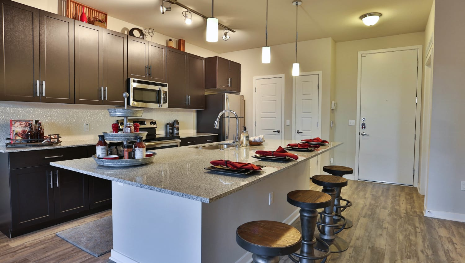 Hardwood flooring and stainless-steel appliances in a model apartment's gourmet kitchen at Olympus Steelyard in Chandler, Arizona