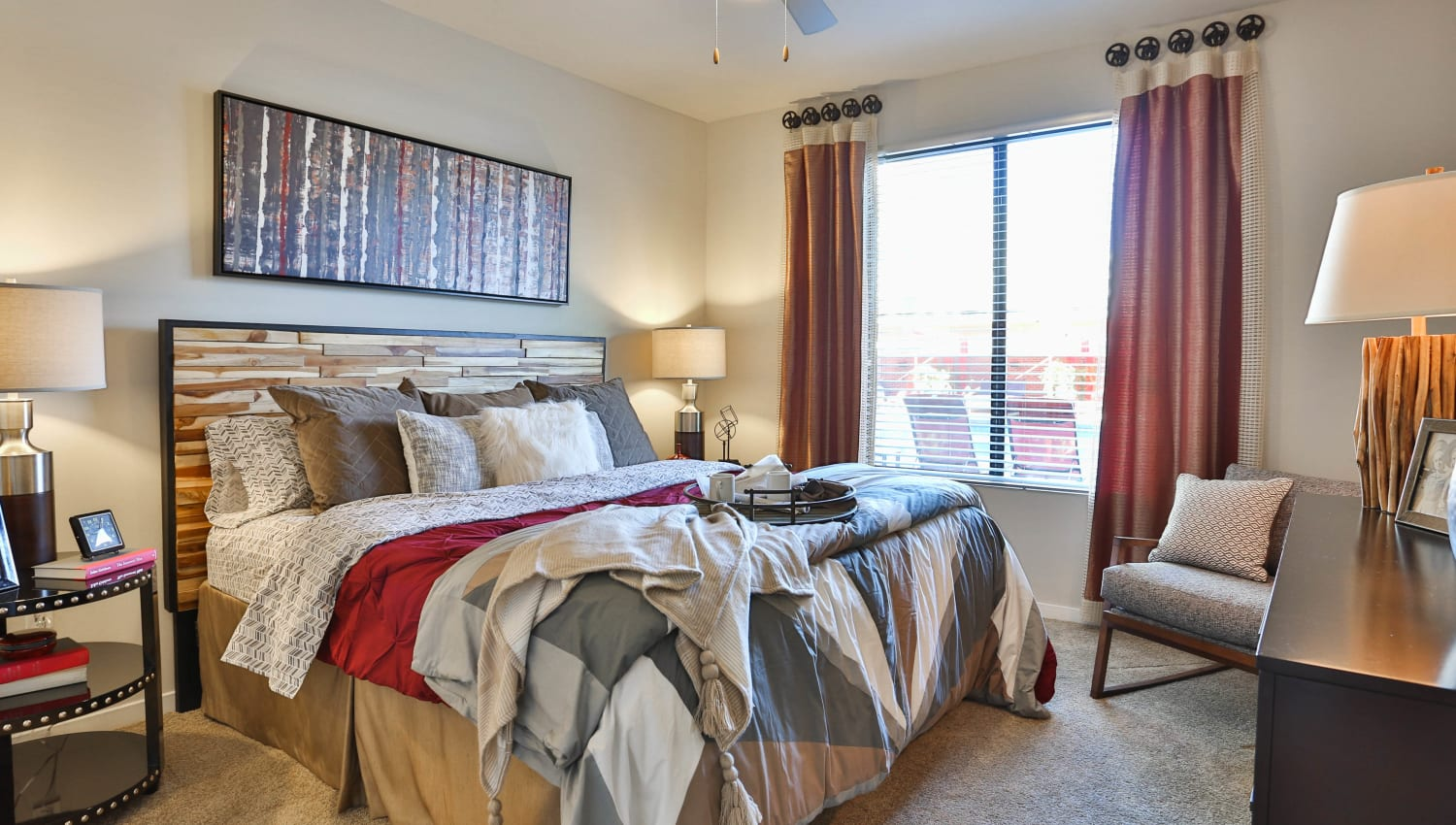 Well-furnished master bedroom in a model apartment at Olympus Steelyard in Chandler, Arizona