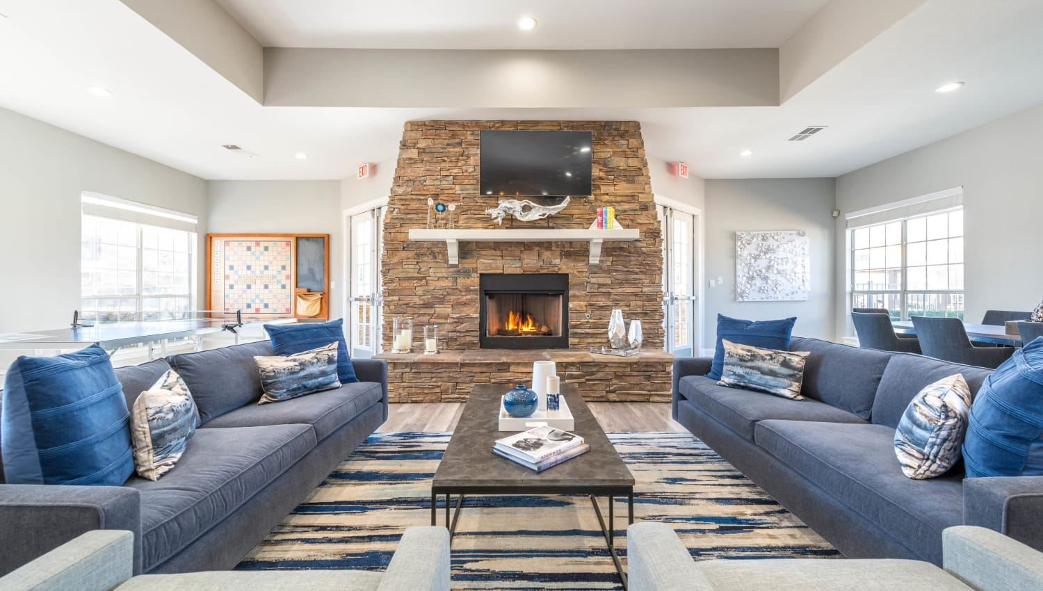 Luxurious lounge are in front of the fireplace in the resident clubhouse at Olympus Stone Glen in Keller, Texas