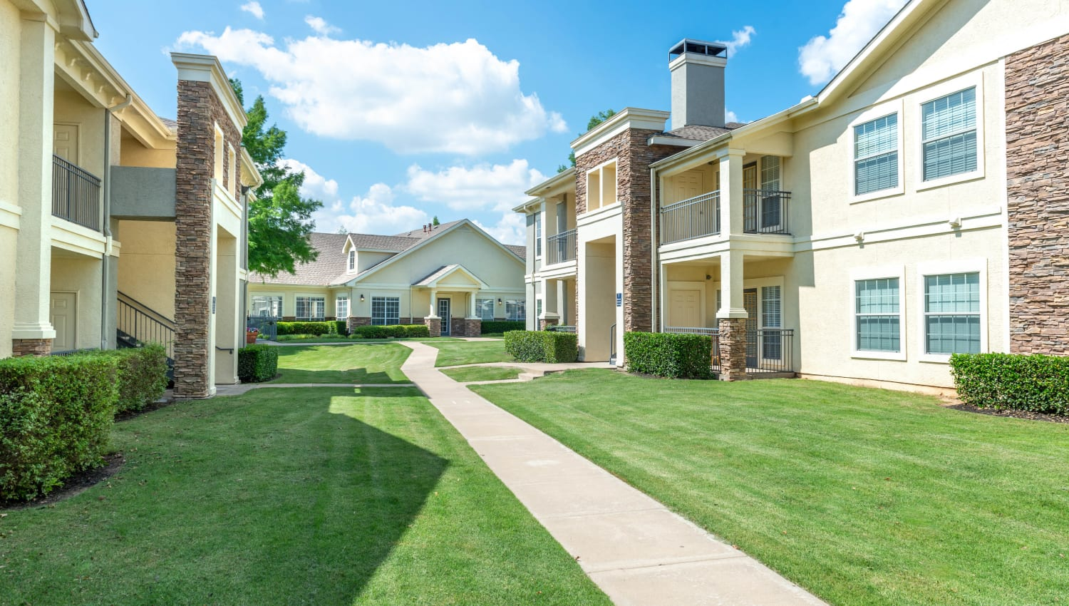 Green grass and manicured shrubberies between resident buildings at Olympus Stone Glen in Keller, Texas