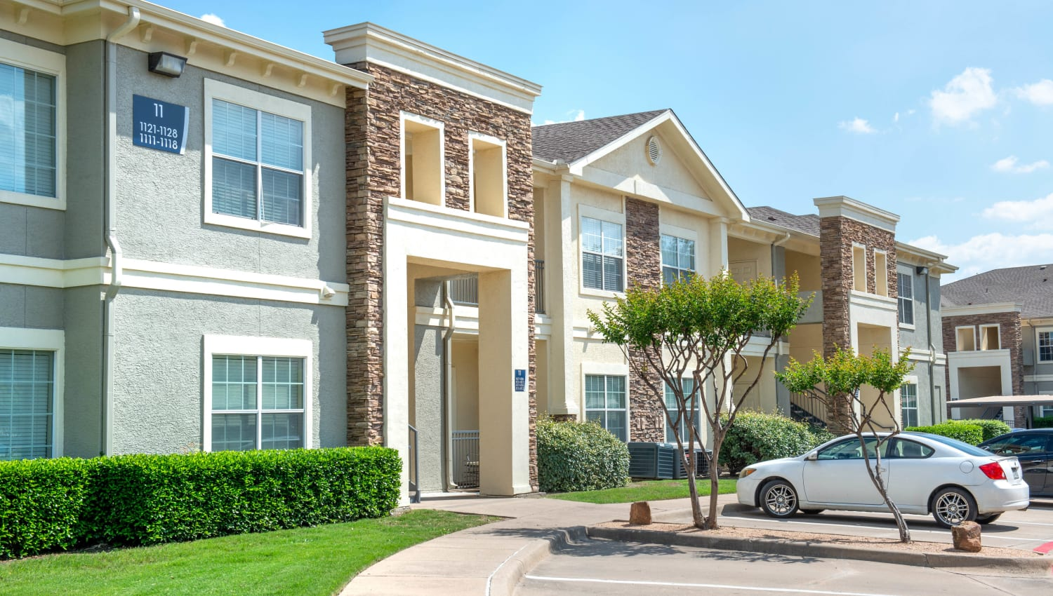 Parking and well-maintained landscaping outside resident buildings at Olympus Stone Glen in Keller, Texas