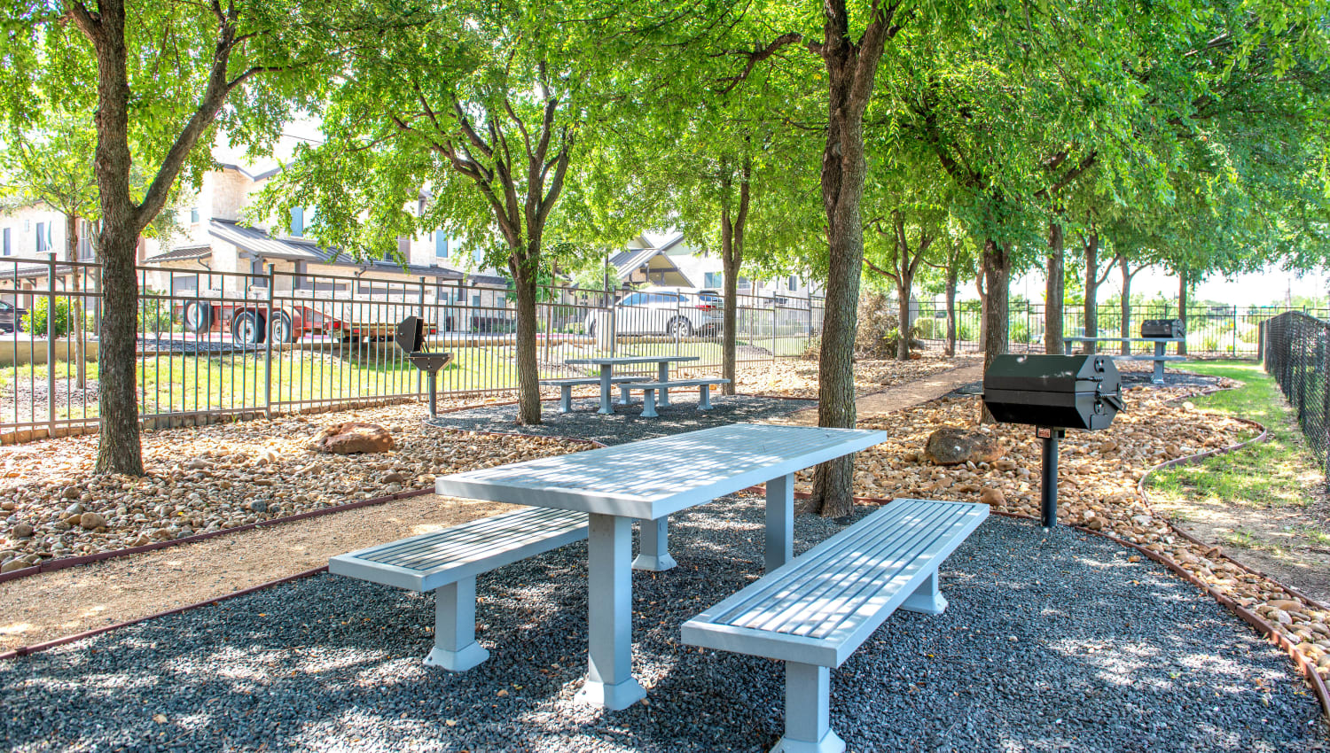 Shaded picnic table at the barbecue area at Olympus Stone Glen in Keller, Texas