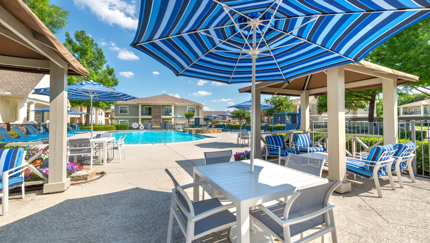 Shaded lounge areas near the pool at Olympus Stone Glen in Keller, Texas