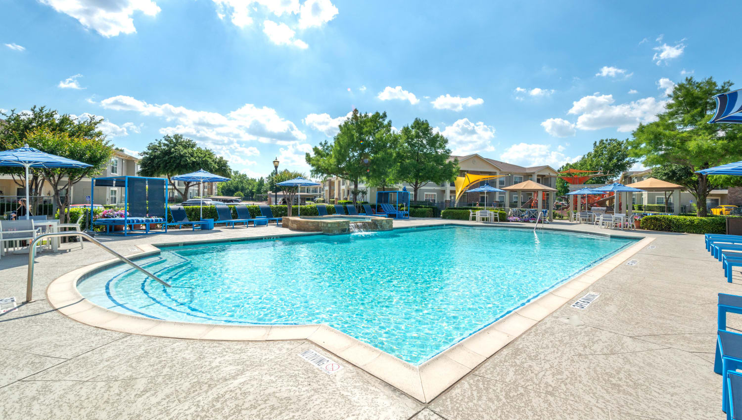 Resort-style swimming pool on a gorgeous day at Olympus Stone Glen in Keller, Texas