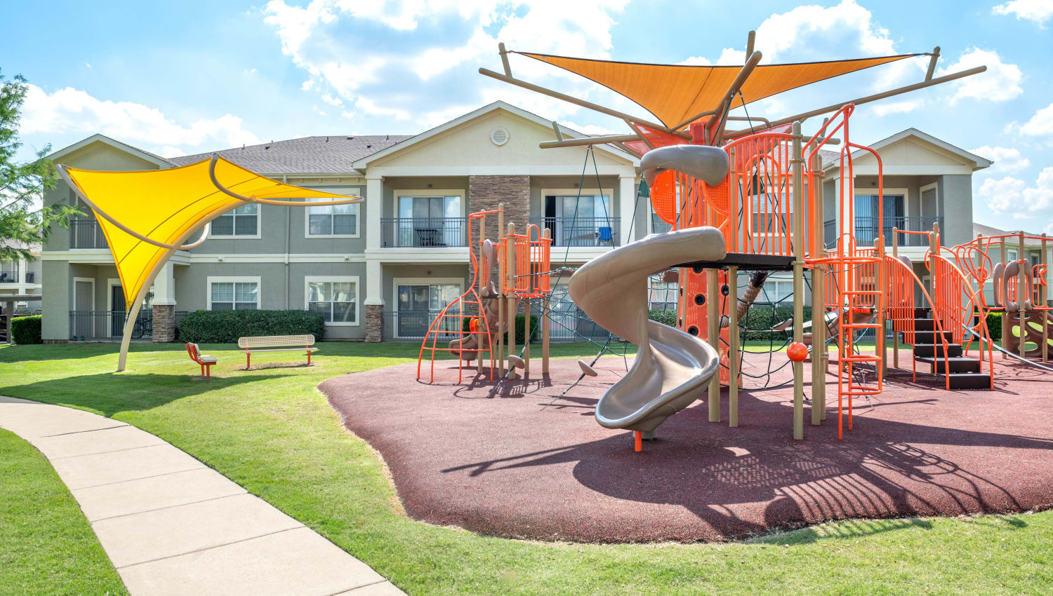 Onsite children's playground with shaded seating nearby at Olympus Stone Glen in Keller, Texas