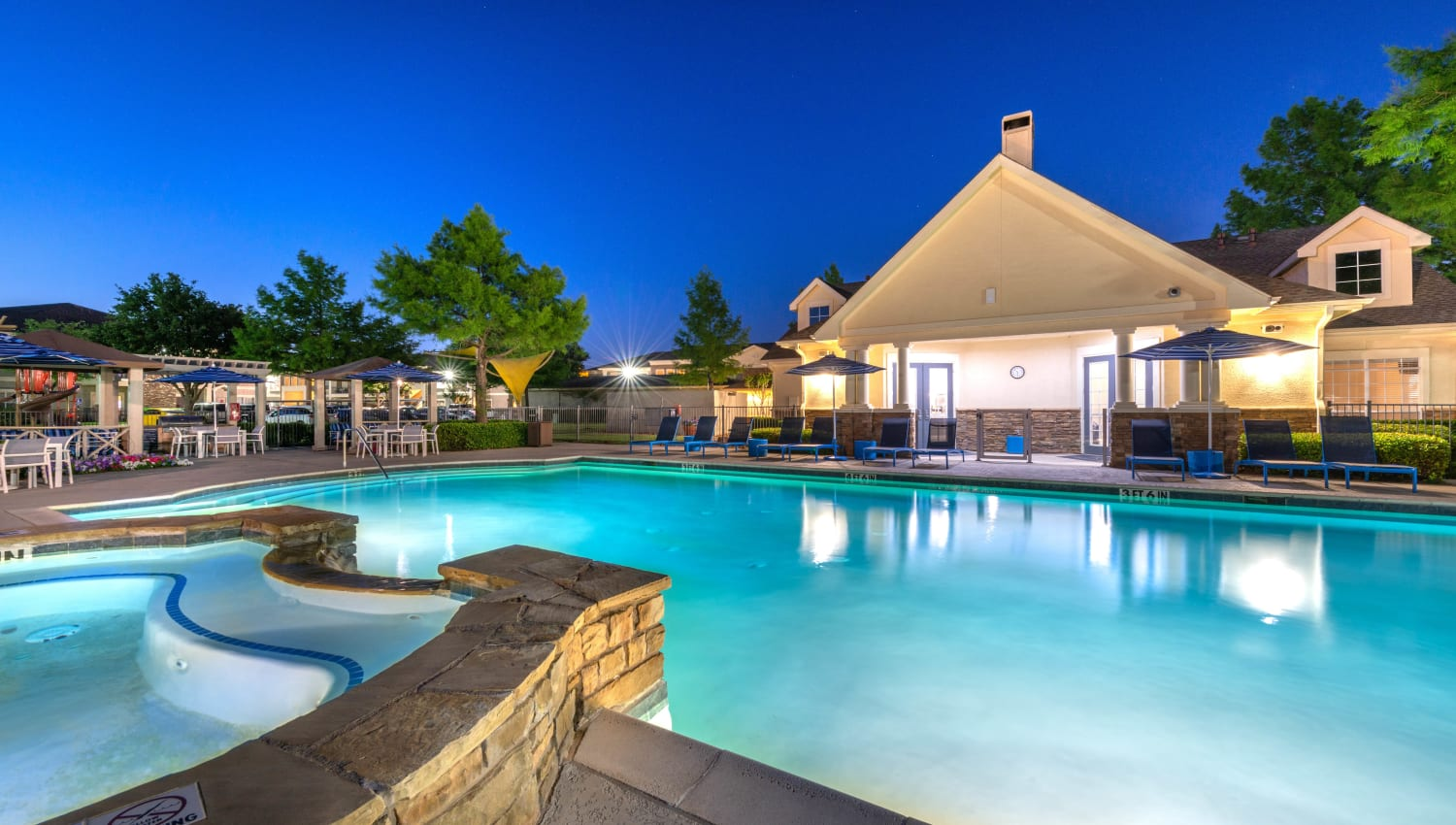 Spa and swimming pool with underwater illumination at dusk at Olympus Stone Glen in Keller, Texas
