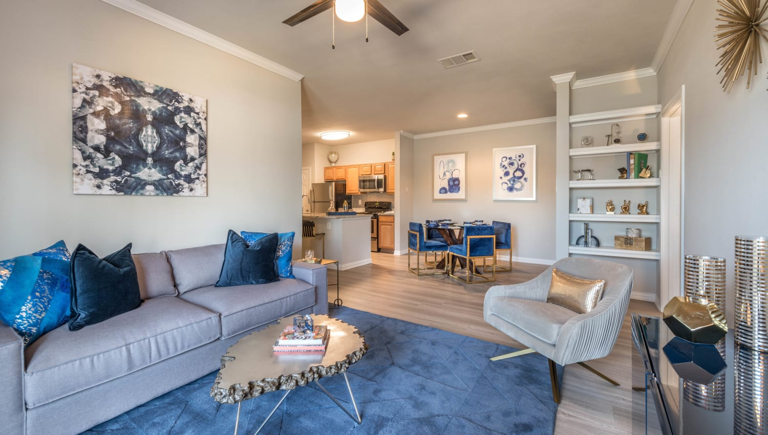 Large open-concept model home's living area with built-in shelving and hardwood floors at Olympus Stone Glen in Keller, Texas