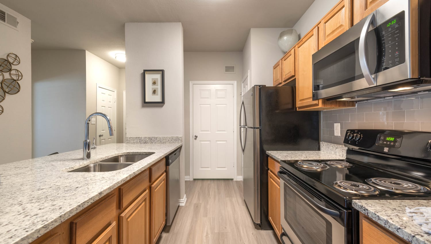 Hardwood flooring, black and stainless-steel appliances, and a pantry in a model apartment's kitchen at Olympus Stone Glen in Keller, Texas
