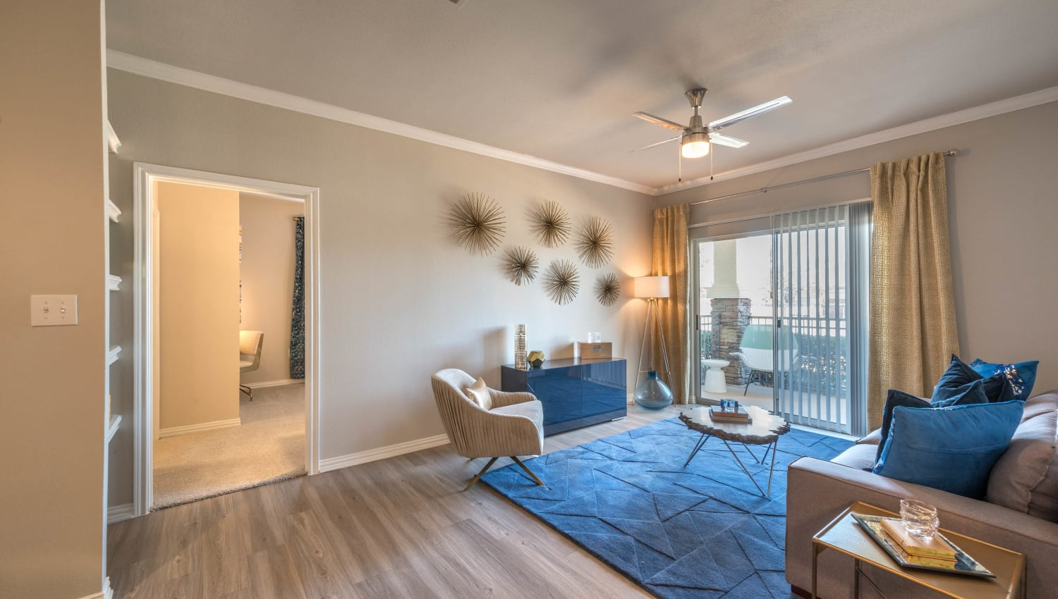 Model home's living area with hardwood flooring and a ceiling fan at Olympus Stone Glen in Keller, Texas