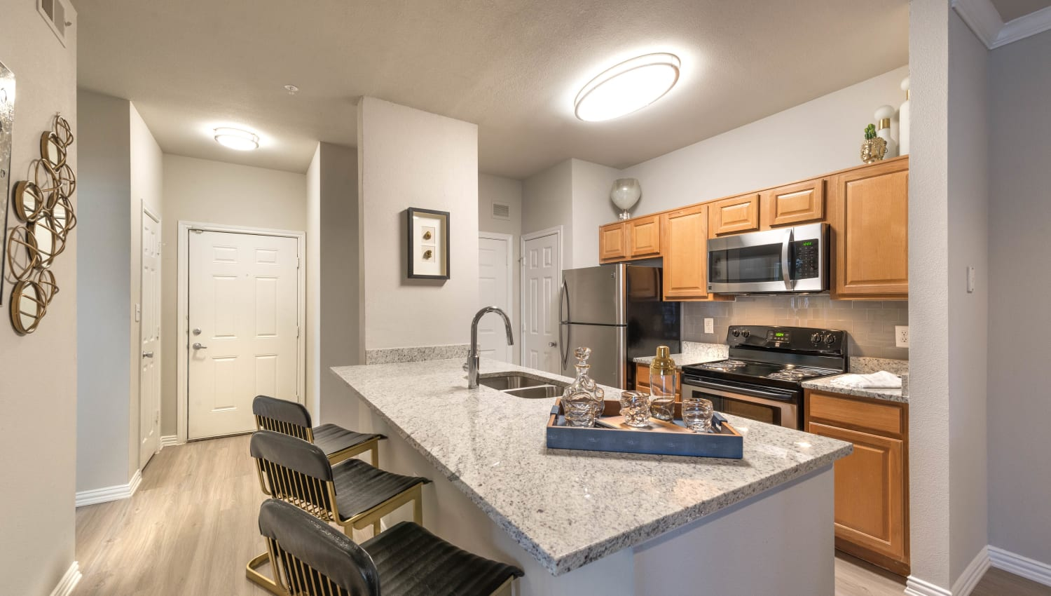 Bar seating at the kitchen island in a model apartment at Olympus Stone Glen in Keller, Texas