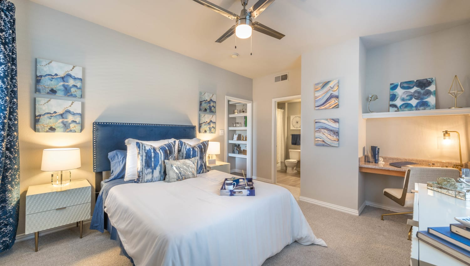 Built-in shelving and desk area in a model home's well-furnished master bedroom at Olympus Stone Glen in Keller, Texas
