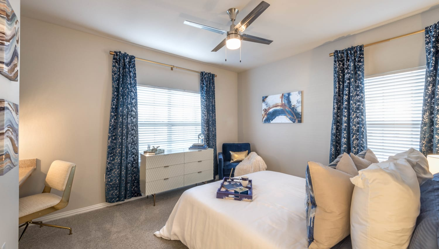 Master bedroom with bay windows and a ceiling fan in a model apartment home at Olympus Stone Glen in Keller, Texas