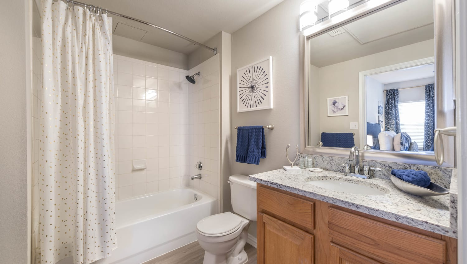 Master bathroom with a granite countertop and large vanity mirror in a model home at Olympus Stone Glen in Keller, Texas