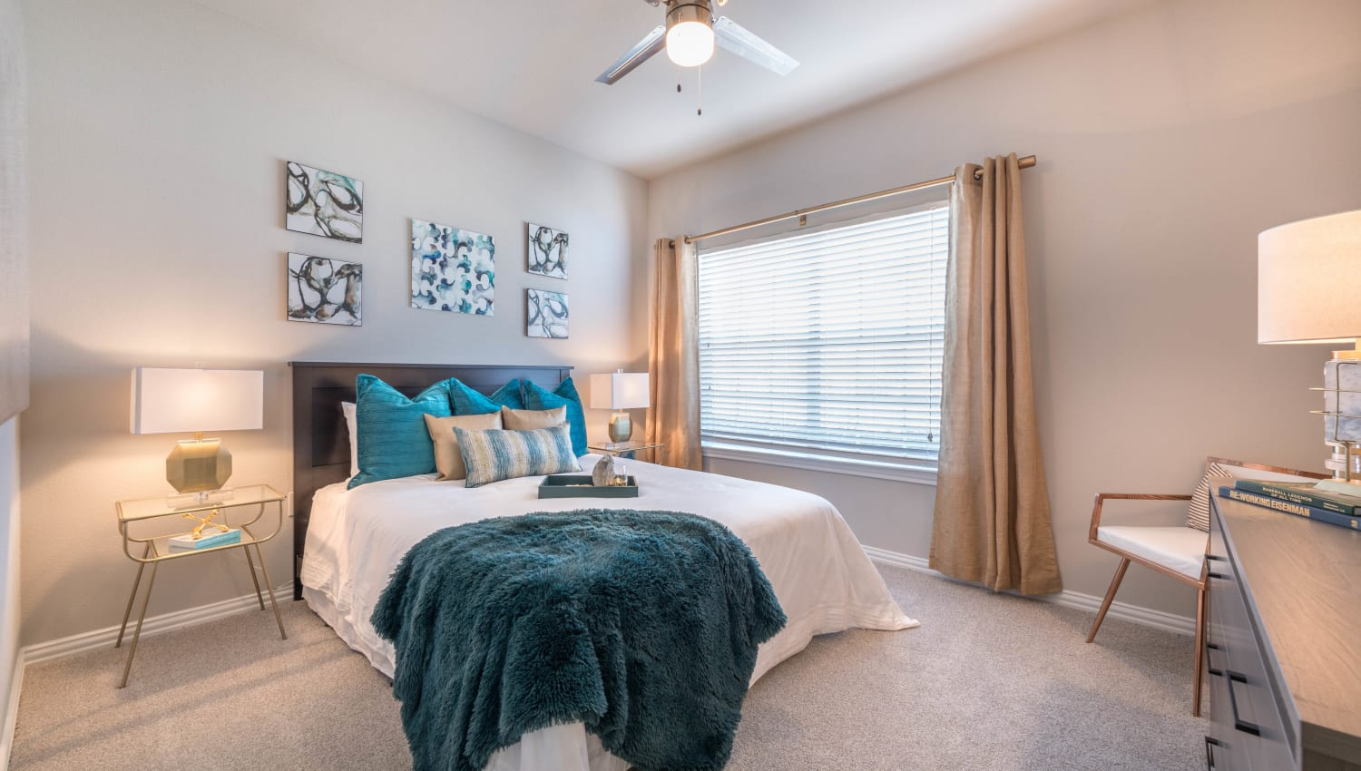 Modern furnishings and a draped bay window in a model apartment's bedroom at Olympus Stone Glen in Keller, Texas