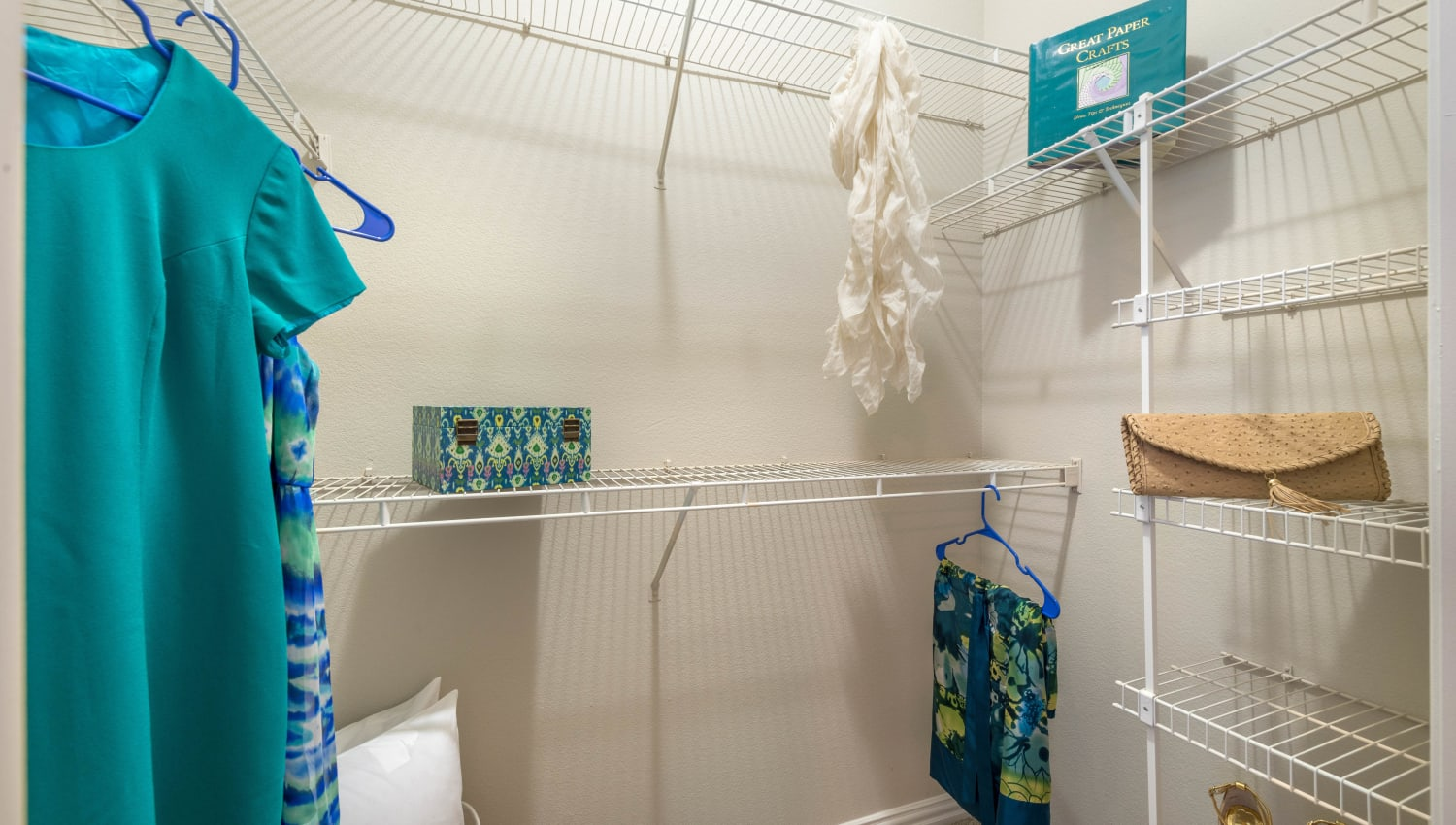 Walk-in closet with built-in shelving in a model home at Olympus Stone Glen in Keller, Texas