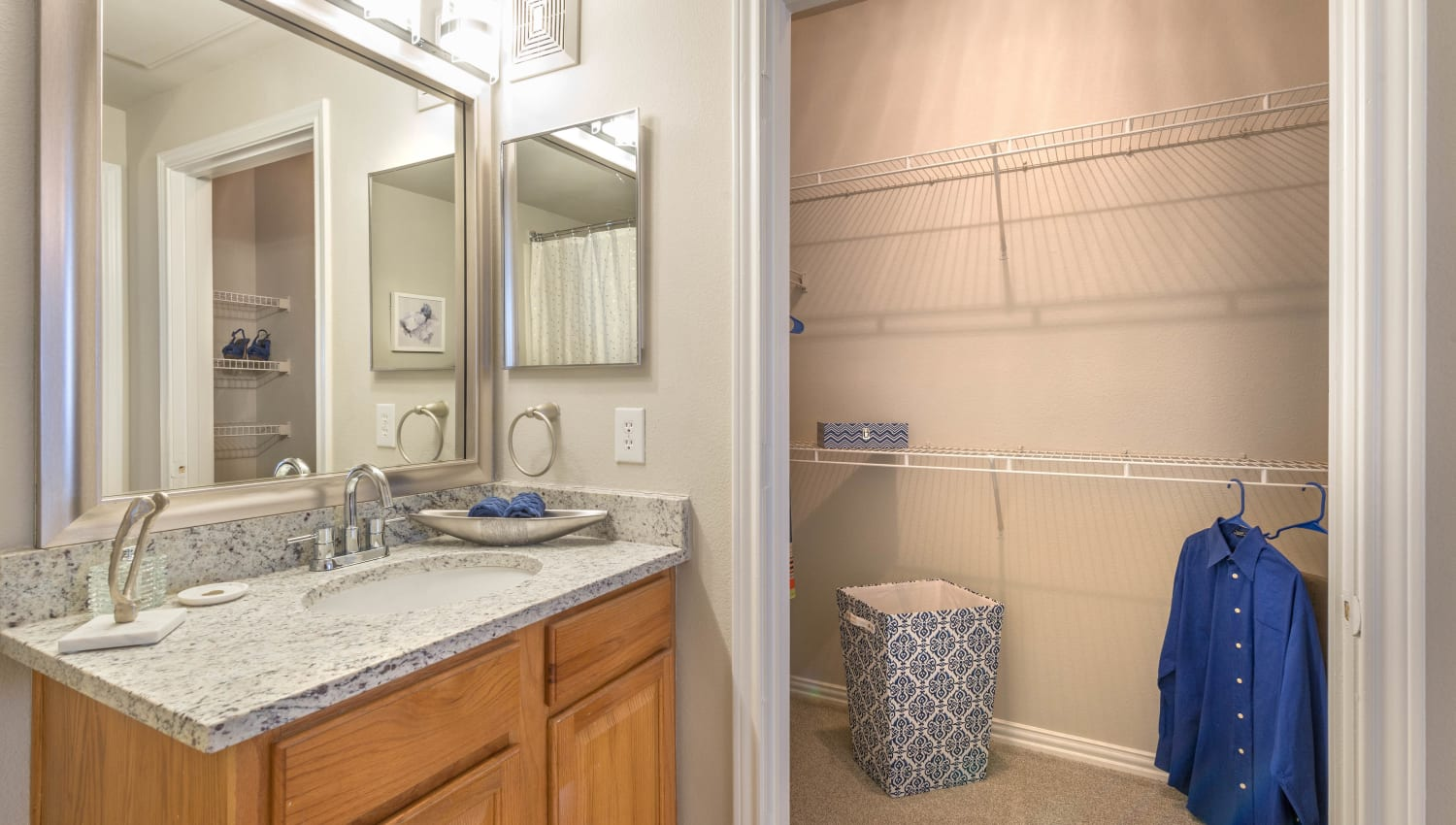 Model home's bathroom with a walk-in closet at Olympus Stone Glen in Keller, Texas