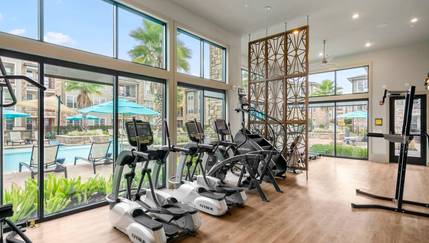 Treadmills and large glass windows in gym at Olympus Grand Crossing in Katy, Texas