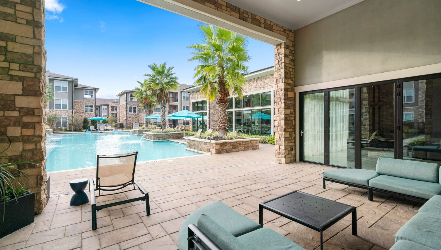 Recliner chair and sofa by pool at Olympus Grand Crossing in Katy, Texas