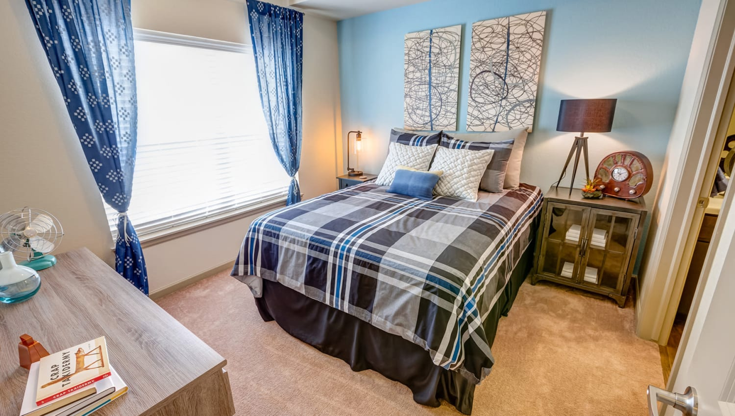 Model home's bedroom with draped windows and an accent wall at Granite 550 in Casper, Wyoming
