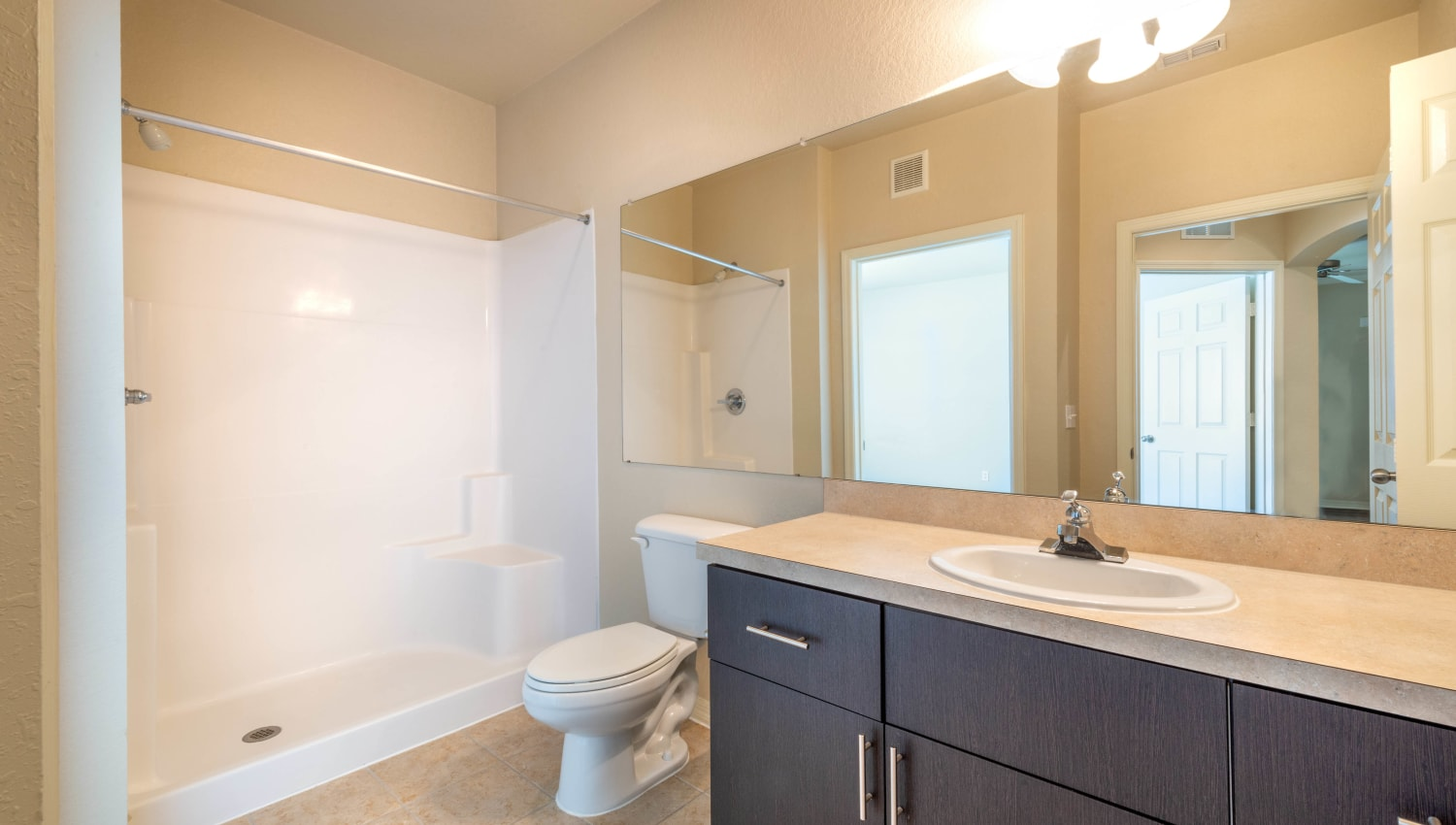 Tiled shower and granite countertop in a model apartment's bathroom at Mirador & Stovall at River City in Jacksonville, Florida
