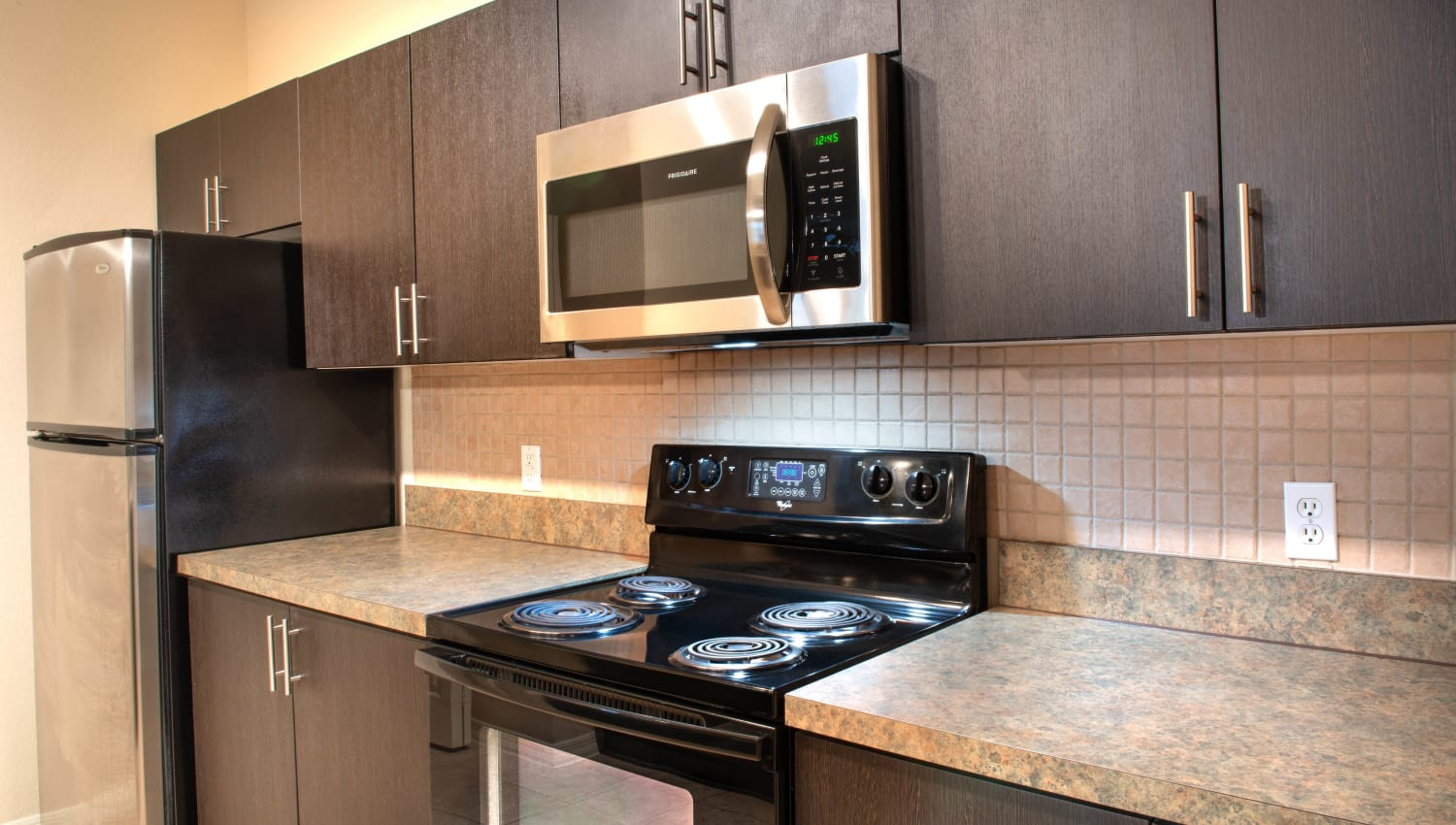 Dark wood cabinetry and stainless-steel appliances in a model home's kitchen at Mirador & Stovall at River City in Jacksonville, Florida