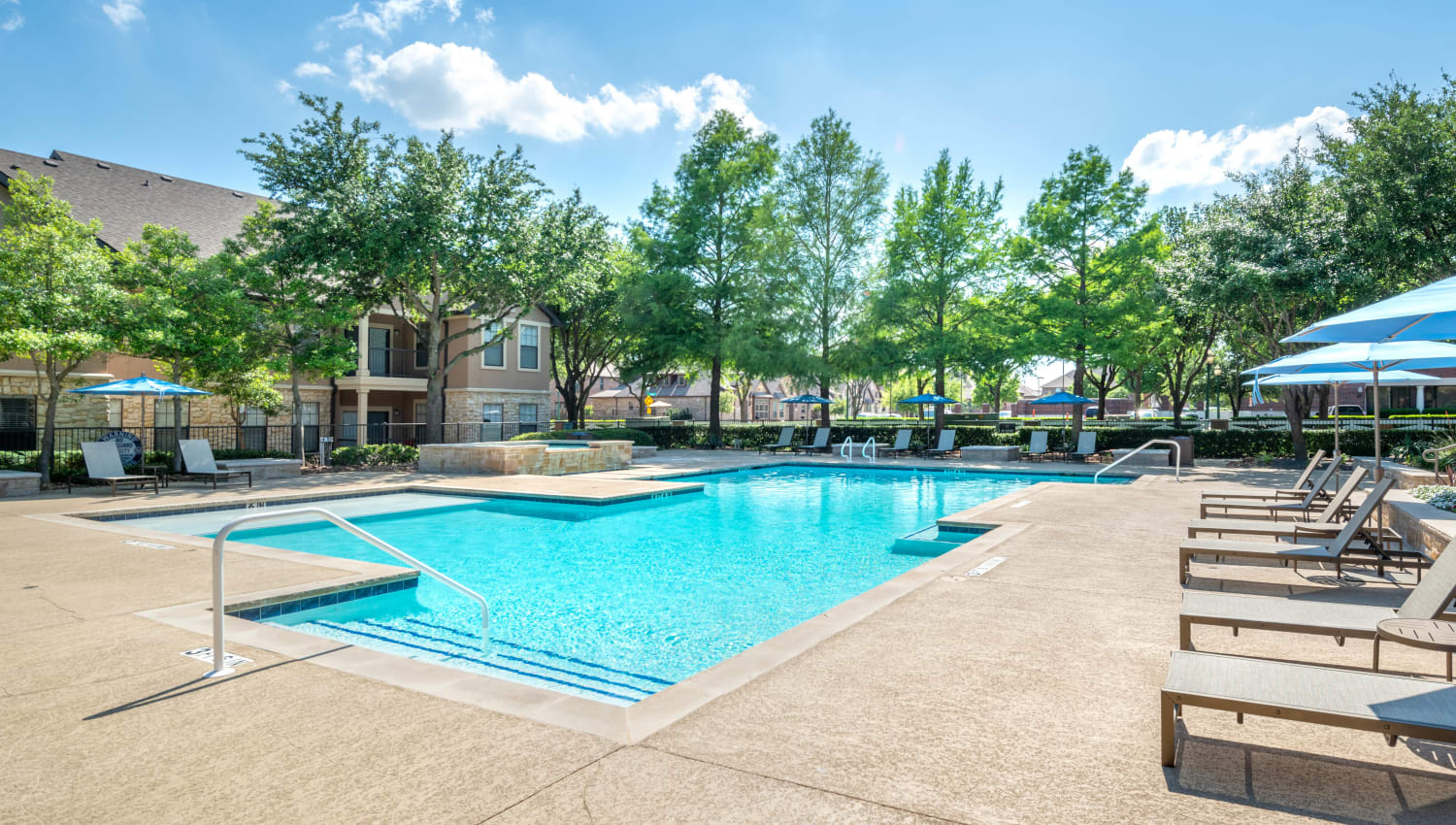 Swimming pool flanked by mature trees at Olympus Town Center in Keller, Texas