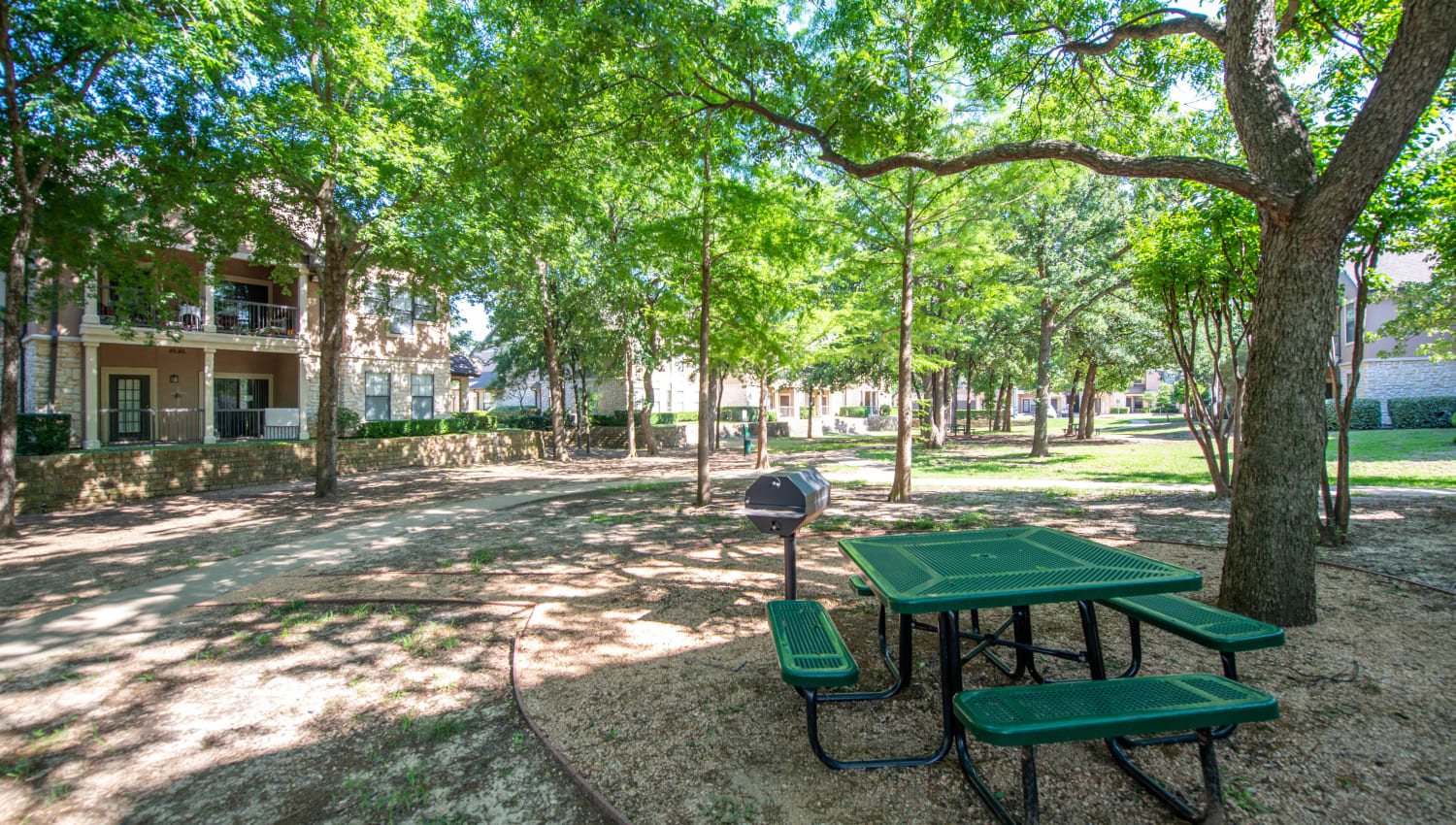 Picnic table shaded by mature trees at Olympus Town Center in Keller, Texas