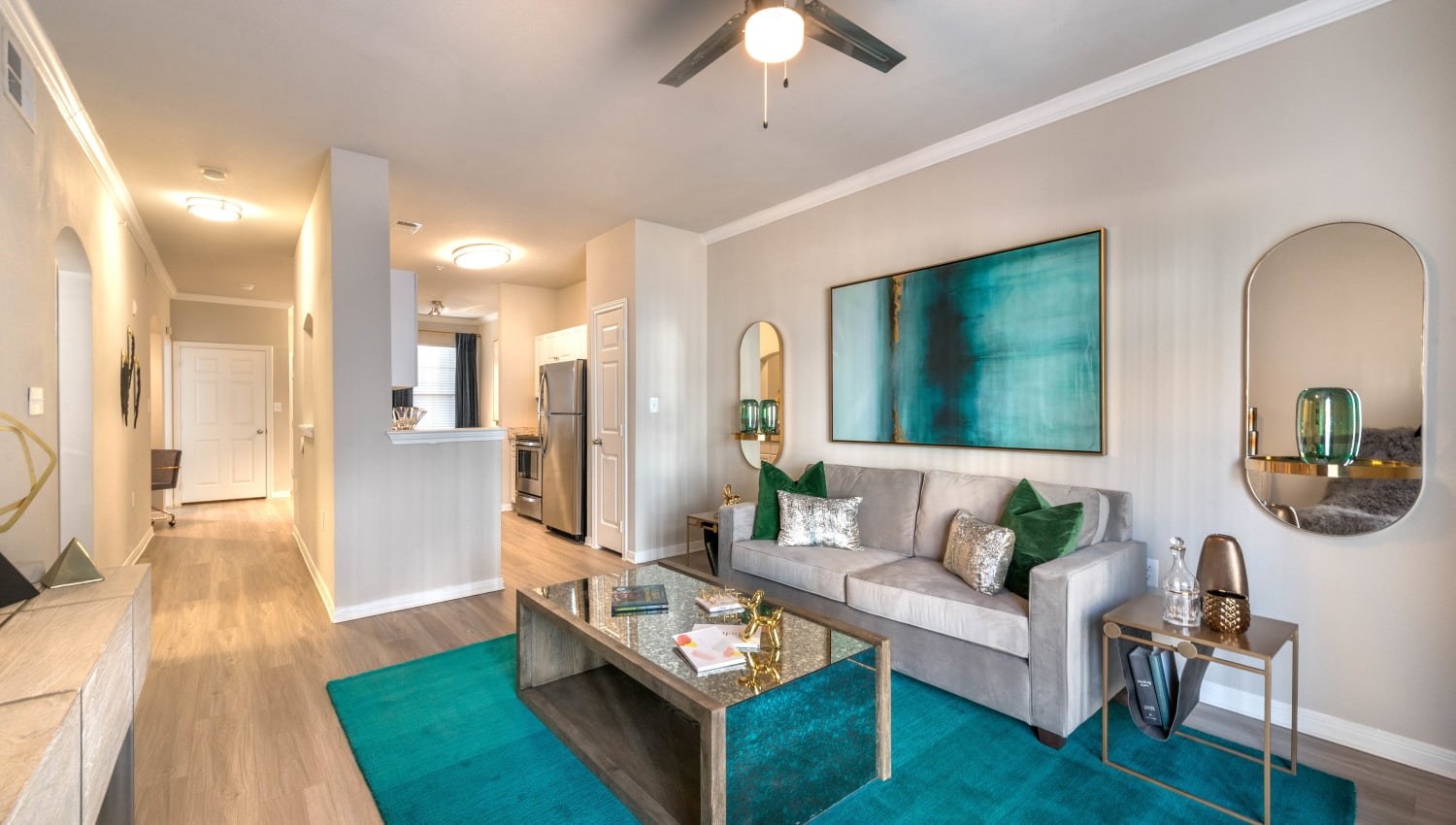 Large open-concept model home with hardwood floors and a ceiling fan in the living area atOlympus Town Center in Keller, Texas