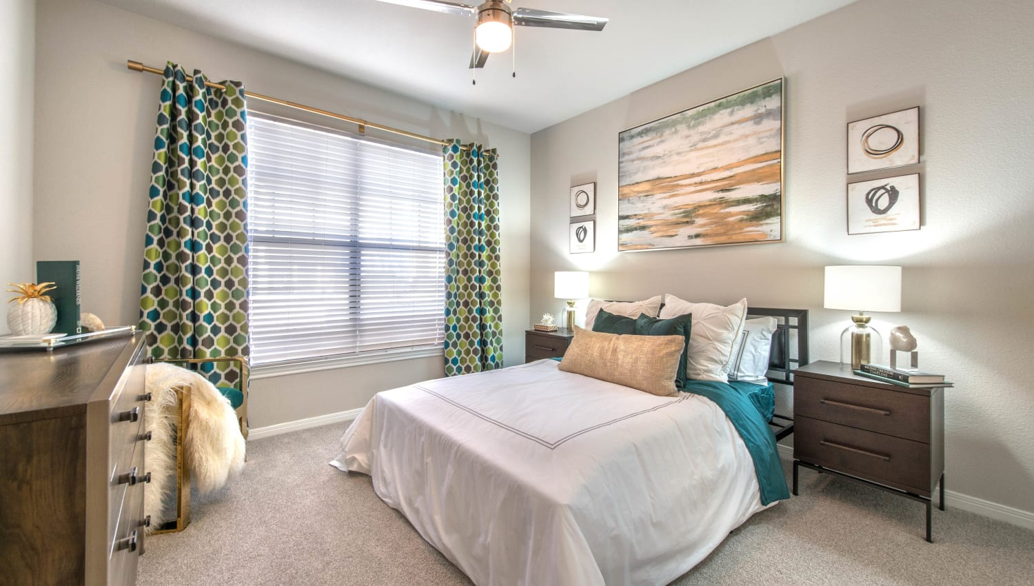 Draped bay windows and a ceiling fan in a model apartment's master bedroom at Olympus Town Center in Keller, Texas