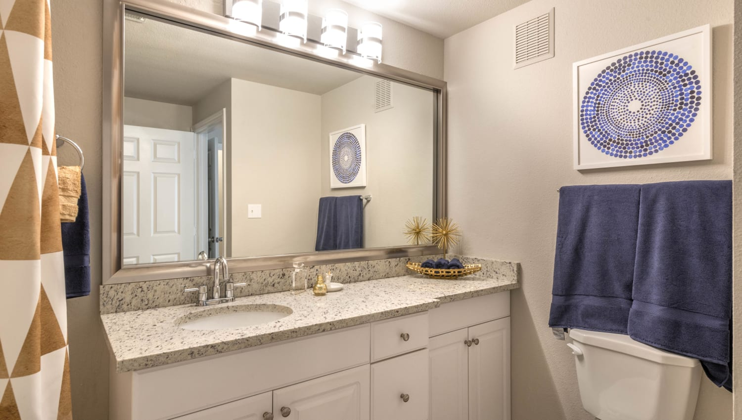 Granite countertop in a model apartment's bathroom at Olympus Town Center in Keller, Texas